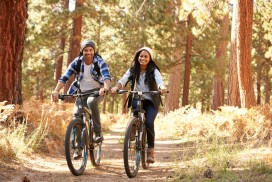 African American Couple Cycling Through Fall Woodland